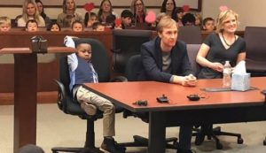 """Οι συμμαθητές του Μάικλ βρέθηκαν όλοι στο πλευρό του στο δικαστήριο, όπου πραγματοποιήθηκε η επίσημη υιοθεσία του από τη νέα του οικογένεια. Στη φωτογραφία που δημοσίευσε η κοσμητεία του Κεντ, φαίνεται ο μικρός Μάικλ μαζί με τους θετούς του γονείς, ενώ πίσω κάθονται όλοι οι """"καλεσμένοι"""" του 5χρονου. Όταν η διαδικασία ολοκληρώθηκε, ο Μάικλ, οι φίλοι του, οι γονείς του και οι δάσκαλοί του, ξέσπασαν σε χειροκροτήματα και αγκαλιές, ενώ φωτογραφήθηκαν όλοι μαζί."""